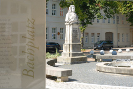 Im Foto sieht man das Bachdenkmal in Köthen ganz in weiß auf einem hohen Sockel, Bach bis zum Gürtel. Links sehr dominant im Vordergrund die Hinweistafel zum Bachplatz. Dahinter ein sehr großes Haus.
