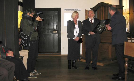 Zur Meldung zum Thema Johann Sebatsian Bach. Renate und Elmar von Kolson nehmen die Ehrungen entgegen. Ein Fotografm links fotografiert den Event. Man sieht auch Publikum, aber nur die Kniee.