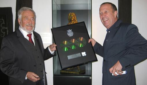 Zur NAchricht das Bild: Elmar von Kolosn präsentiert stolz die Platin-CD für Johann Sebastian Bach. Rechts im Bild der belgische Moderator von Klara, Klassik-Ratio.