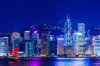 Im Bild sieht man die Wolkentratzer-Skyline von Hongkong. Auch in Honkong gibt es einen Bachchor. Hinter den Hochhäusern sieht man einen Berg, vorne ist Gewässer. Blau überwiegt in diesem Nachtmotiv, der Himmel ist dunkles royalblau.