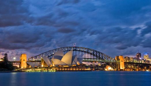 Das Bild zeigt die Skyline von Sydney mit der Oper bei Nacht. Der Himmel ist stark bewölkt. Auch Sidney hat einen Bachchor. Hinter der Oper sieht man die berühmte Brücke. Die Oper ist beleuchtet. Das komplette Foto hat einen Blau-Touch.