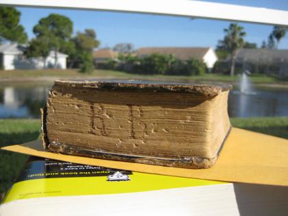 Auf dem Foto sieht man das uralte Gesangbuch schräg fotografiert auf einem Dummy-Buch zum späteren Nachbearbeiten, im Hintergrund ein See. Man sieht die Buchstaben R und B auf den Seiten eingeritzt.