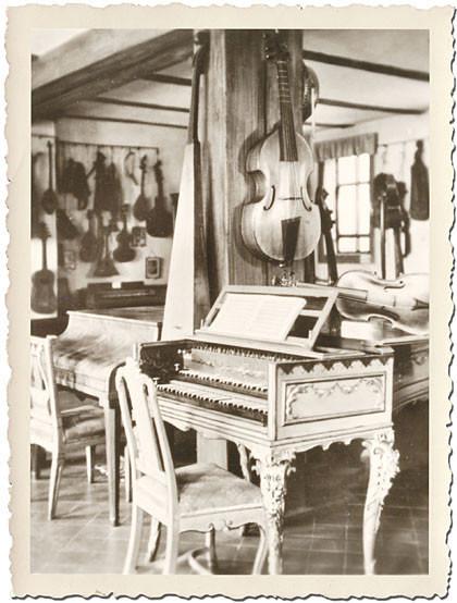 Schwarzweiß mit weißem Riffel-Rand und alt: Im Steckbrief-Foto sieht man ein Cembalo, ein Klavier und viele Streichinstrumente an den Wänden: Alle spielte Johann Sebastian Bach.
