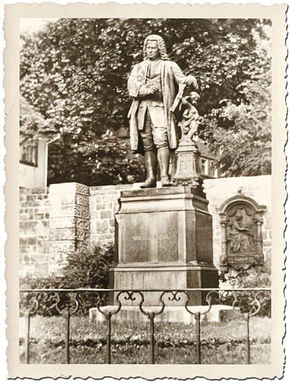 Eine Postkarte von 1901 zum Steckbrief von Johann Sebastian Bach in Eisenach. Das historische Foto ist schwarzweiß und hat einen geriffelten Rand. Vorne sieht man ein Blumenbeet durch ein Ziergitter abgesperrt. Bach steht auf einem Podest, beides ist rund