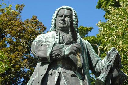 Das Foto zeigt das Bach Denkmal in Eisenach vom Gürtel aufwärts. Bach hält eine Schreibfeder und hält sich an einem Buch. Im Hintergrund Bäume und blauer Himmel. Sonne scheint auf das Denkmal.