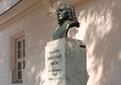 Das Bach Denkmal in Weimar als Foto: auf einem gewaltigen Sockel ist die Büste von Bach. Dahinter ein Haus, die Sonne scheint aufs Denkmal. Man sieht den Namen und die zwei Zeiten in Weimar.