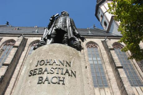 Im Bild ist das Denkmal von Bach vor der Thomaskirche imposant extrem von nah und unten fotografiert: der Schriftzug extrem groß, der Kopf weit entfernt. Im Hintergrund die Kirche, blauer Himmel.