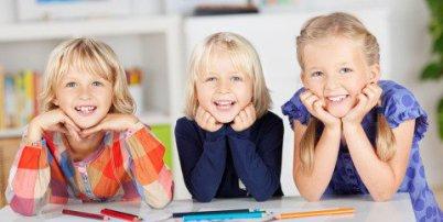 Drei kleine Mädchen haben die Köpfe auf einem Tisch auf die Hände gestützt und lachen und lächeln herzlich zur Kamera. Im Vordergrund siehrt man Mal-Utensielien und alle haben farbige Kleidung an.