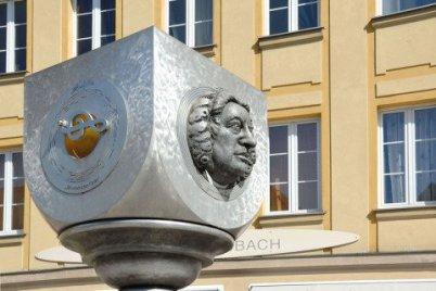 Das Bach Denkmal in Ansbach: es ist aus Metall, es ist silbern und es ist modern. Im Hintergrund am Haus sieht man den Namen Bach, der aber vom bayerischen Namen der Stadt Ansbach herrührt.