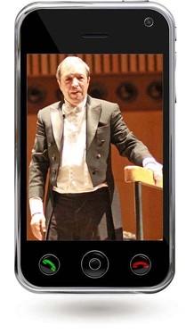 Das Bild zum Zitat zu Bach: Perahia steht für ein Foto - ein Farbfoto. Eine Hand lehnt auf einem Geländer. Er hat Frack an. Das Bild ist montiert in das Display eines schwarzen Smartphones.