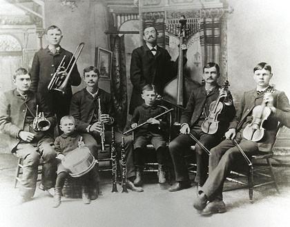 Das Bild zeigt die historische Bach-Band in Rochester, wohl Vorläufer von jedem Bachchor und Bachorchester. Es ist eine historische schwarzweiße Aufnahme. 7 Kinder und ein Mann sind zu sehen. Alle haben Instrumente, 6 Kids sitzen vorne, 1 Kind steht dahin