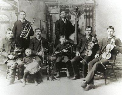 Das Schwarz/weiß Foto einer Band, der Bach Band in USA. 8 Personen, davon 7 Kinder unter 25. Alle haben Instrumente. Sechs sitzen, dahinter eine Orgel. In der Mitte hinten: Reinhold Bach mit Bratsche.