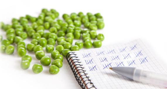 Man sieht eine Illustration aus Block mit Strichzählung sowie einen Kugelschreiber und hellgrüne Erbsen als Stilleben. Der Block hat eine Spiralbindung und vom Kugelschreiber ist nur wenig zu sehen.