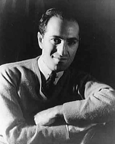 Gershwin hat beide Arme verschränkt und schmunzelt zur Kamera. Die aufnahme ist schwarz/weiß, er trägt ein Hemd mit Krawatte und eine Jacke darüber.