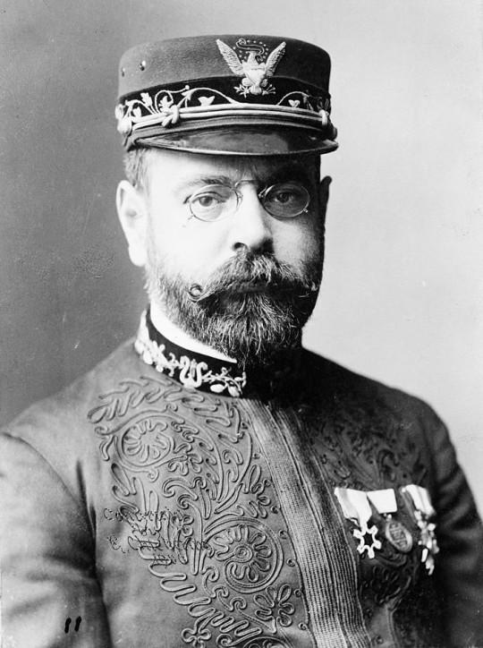 Sousa in Uniform schaut streng in die Kamera. Er trägt eine Kappe mit Adler, zwei Orden am Jacket und hat einen Vollbart, dess Spitzen am Schnauzer sich rollen.