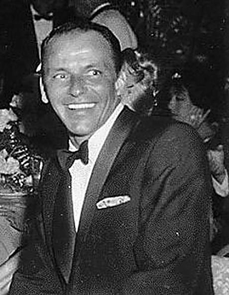 In einer schwarzweißen Aufnahme lacht Frank Sinatra an der Kamera vorbei. Herr trägt weißes Hemd und scharzes Jacket, Fliege und Einstecktuch.