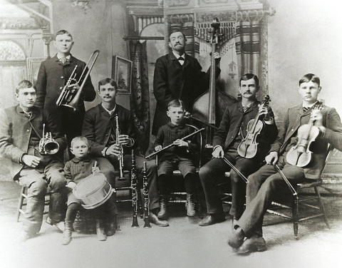 Man sieht auf einem historischen schwarz-weißen Foto die Bach Band aus Rochester: Johann Friedrich August Bach und seine 7 Söhne. 6 Personen sitzen, der Vater und 1 Sohn stehen im Hintergrund.