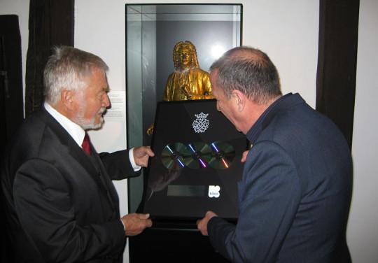 Zur Meldung das Foto: Vor einer Glasvitrine mit einer Goldfigut von Johann Sebastian Bach halten E. von Kolson und der belgische Radiomoderator die Platin-CD.