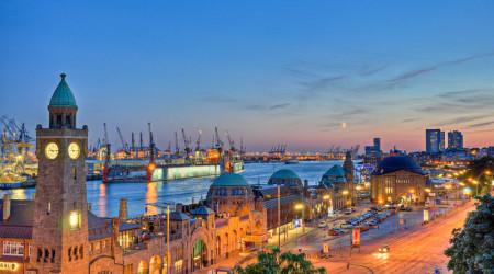 Im Bild sieht man den Hamburger Hafen kurz nach der Dämmerung. Hamburg ist Heimat mehrerer Bachchöre und Bachorchester. Man sieht die Landungsbrücken, sowie die Elbe und im Hintergund Hafen-Industrie..