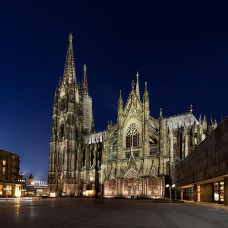 Im Bild die Nachtaufnahme des Kölner Doms. Köln ist eine Stadt, in der es einen Bachchor gibt. Das Foto ist in der blauen Stunde fotografiert. Man sieht vorne die Domplatte, oben den blauschwarzen Himmel.