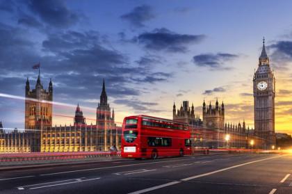 Im Bild sieht man die Parlamentsgebäude in London kurz vor Sonnenuntergang. Ein roter Doppeldecker-Bus ist verwischt fotografiert. In London gibt es mehr als einen Bachchor.