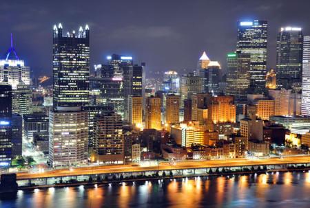 Das Bild zeigt Pittsburgh in den USA bei Nacht. Pittsburgh hat einen Bachchor. Man sieht die Skyline aus Wolkenkratzern am Rand eines Gewässers.. Der Himmel ist bedeckt und blau-grau.
