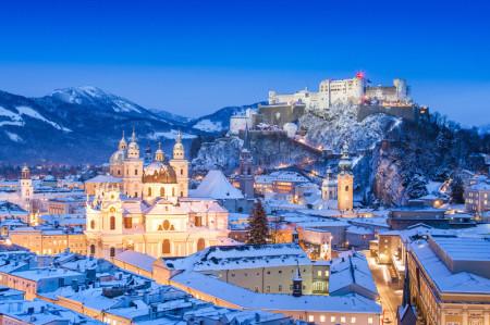 Die Mozartstadt Salzburg hat einen Bachchor. Man sieht Salzburg im Schnee am frühen Abend. Alle Häuser sind erleuchtet. Es ist ein Wintermärchenbild. Im Bild oben ist die Festung Salzburg, darüber der tiefblaue Himmel.