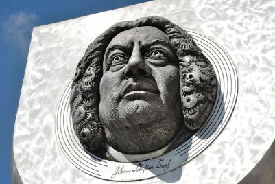 Im Bild sieht man das Bach Denkmal von der Seite: der Kopf ist riesig. Im Hintergrund ist ein gelbes barockes Haus zu sehen, oben einige Blätter, die Sonne scheint.