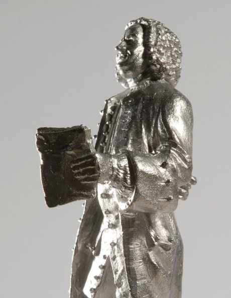 Johann Sebastian Bach als Zinnfigur. Der Aufnahmewinkel ist von der Seite und die Beleuchtung ist extrem