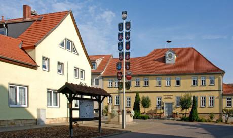 Die Ortsmitte von Wechmar, neben dem Bach Haus ist die Gaststätte Löwe. Im Vordergrund eine Hinweistafel, daneben ein prächtiger Maibaum. Die Sonne scheint und man sieht einen hübschen Brunnen.