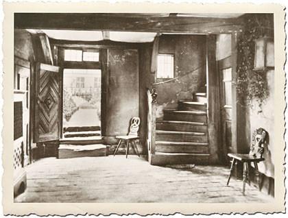 Steckbrief Bild vier: schwarz-weiß, weißer Riffel-Rand: der Hausflur vom Bachhaus Eisenach. Rechts die Treppe, man sieht zwei Stühle, alles ist sehr niedrig. Von hier gelangte Johann Sebastian Bach in den Garten hinter dem Bachhaus, den man durch die offe