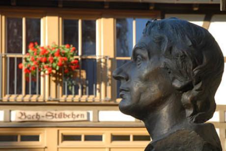 """Im Bild sieht man den Kopf des ganz kungen Bach vor dem Fachwerkhaus mit dem Schriftzug """"Bach-Stübchen"""" und roten Geranien. Bach ist sehr nah fotografiert und blickt nach links. Sonnenschein."""
