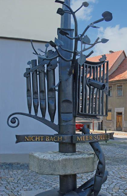 """Das Bach-Denkmal in Ohrdruf. Nicht die Person, sondern es sind Orgelpfeifen und ein Spruchband mit den Worten """"Nicht Bach, Meer sollte.."""". Das Denkmal ist im Schatten. Wolken, Sonne."""