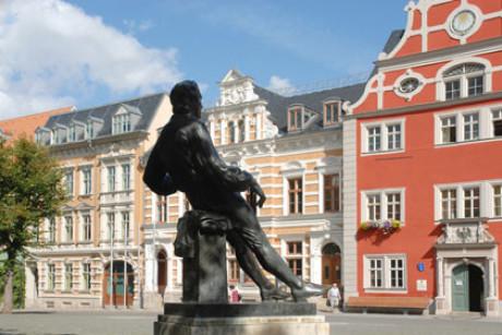 Auf dem Foto sieht man das Denkmal von Bach in Arnstadt von der Rückseite, als Art Schattenriss vor den alten Marktplatz-Gebäuden. Bach sitzt auf dem Sockel, leger. Sonne, Wolken, blauer Himmel.