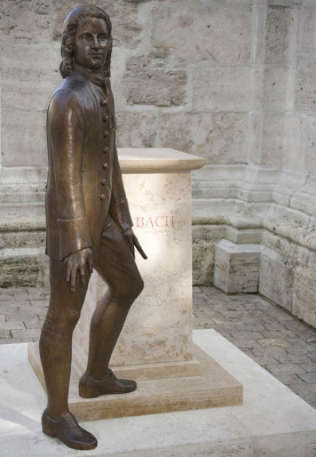 Der sehr junge Bach als Denkmal. Er steht neben seinem Sockel vor einem glatten Stück Kirchenwand. Er spreizt auf dem Foto die Hände und Arme ab. und schaut zum Betrachter. Er steht im Schatten.