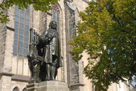 Im Foto ist das bekannteste Bach Denkmal in Leipzig vor der Thomaskirche fotografiert. Man sieht nur wenig vom Sockel, im Hintergrund Kirchenfenster, rechts ein Baum, die Sonne scheint.