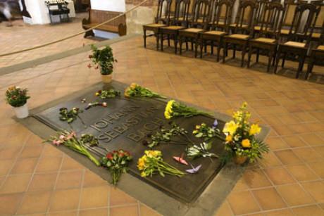 Im Foto sieht man die Grabplatte von Johann Sebastian Bach in der Thomaskirche. Rund herum braune Fliesen, im Hintergrund eine Stuhlreihe, der Bereich ist durch eine Kordel abgesperrt.