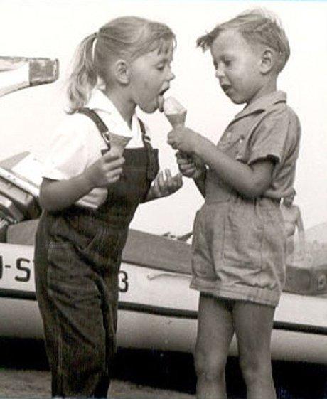 Auf einem 50 Jahre alten schwarz-weißen Bild lässt ein Junge mit kurzen Hosen, etwa 10 Jahre alt, ein Mädchen mit einem Pferdeschwanz am Eis lecken. Sie hat eine Latzhose an und hält auch ein Eis.