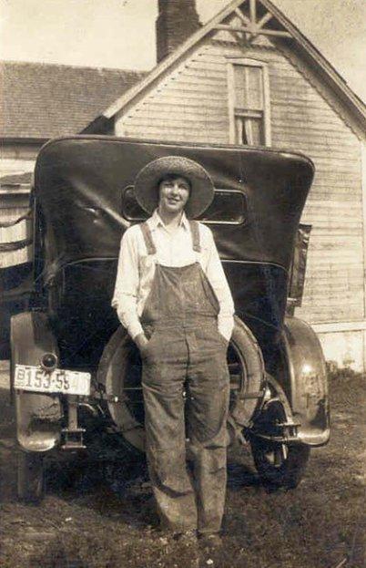 Ein Foto aus Amerika. Etwa 80 alt, scharzweiß. Eine junge Frau steht vor der Rückseite eines uralten Autos. Im Hintergrund ein Haus. Sie hat einen Hut auf, eine Latzhose an, die Hände in den Taschen.