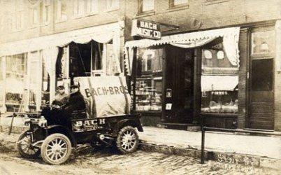 """Auf einem vergilbten schwarz-weißen Foto sieht man einen winzigen US-LKW mit der Aufschrift """"Bach Brothers"""". Vor der Plane ist die Sitzbank offen, zwei Personen sitzen, dahinter ist das alte Bach-Geschäft."""