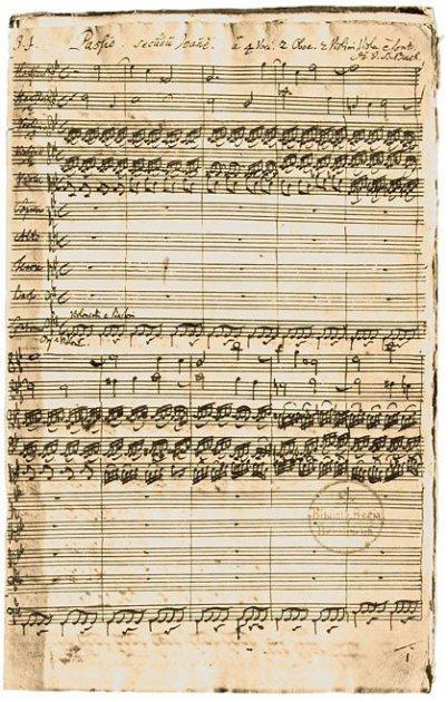 Im Bild sieht man ein 300 Jahre altes Notenblatt, stark vergilbt in der Handschrift von Johann Sebastian Bach. 4 Notenlinien sind beschriftet. Man erkennt einen Stempel, der Rand: zerfleddert.