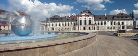 Man sieht im Foto zum Kapitel Ursprung in Bratislava das Schloss und links im Bild einen Brunnen mit silberner großen Erdkugel in der Mitte und senkrechte Fontainen rundherum. Sonne und Kumuluswolken.