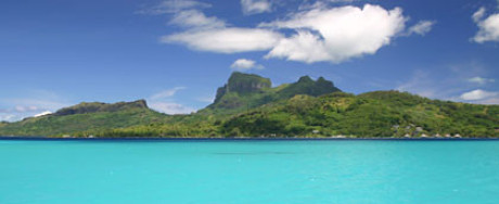 Im Foto zum Kapitel Ursprung sieht man Südsee-Atmosphäre. Das Meer im Vordergrund traumhaft türkis. Hohe aber grüne Berge hinter dem Ufer. Sonne und weiße Wolken.