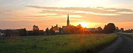 Das Bild im Kapitel Ursprung zeigt Wechmar mit einem grünen Feld im Vordergrund und rechts die gerade aufgehende Sonne neben dem Kirchturm. Es ist ein aktuelles Foto.