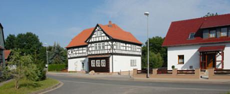 Man sieht im Foto zum Kapitel Ursprung die Veit Bach Mühle und das Nachbarhaus rechts. Davor eines Straße. Die Mühle ist ein Fachwerkbau, davor ist ein Mühlstein.