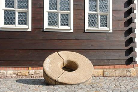 """Im Foto sieht man eine Großaufnahme des Mühlsteines im Kapitel """"Ursprung der musicalisch-Bachischen Familie"""". Er ist ins Pflaster vor der Mühle eingelassen. Der untere Teil der Mühle ist dunkles Holz."""