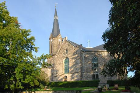 Ein Foto zum Ursprung Kapitel zeigt die Sankt Viti Kirche in Wechmar mit dem hohen Turm. Vorne sind Gräber, rechts und links zwei Bäume, die Ansicht ist von der Rückseite. Sonnenschein und wolkenlos.