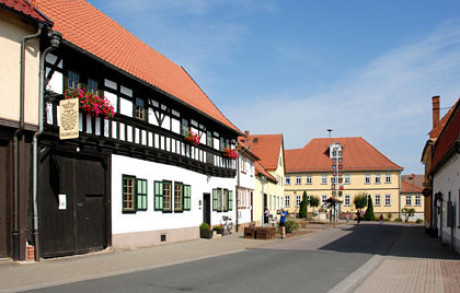Ein Foto vom Bachhaus in Wechmar. Ein Fachwerkbau mit großem Holztor. Davor die komplette Straße. Im Hintergrund Hotel und Gasthof Löwe und ein Maibaum. Am Bachhaus: Geranien. Sonnenschein.