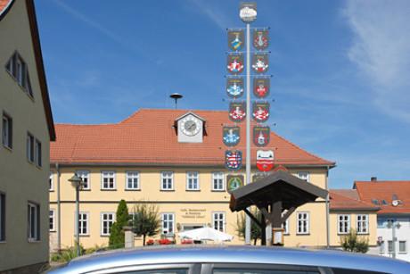 Das Bild zum Ursprung: Man sieht über ein silbernes Autodach hinweg groß das Hotel Löwe und einen mittigen Maibaum. Davor eine Tourist-Info mit Holzüberdachung. Sonnenschein, leichte Schleierbewölkung