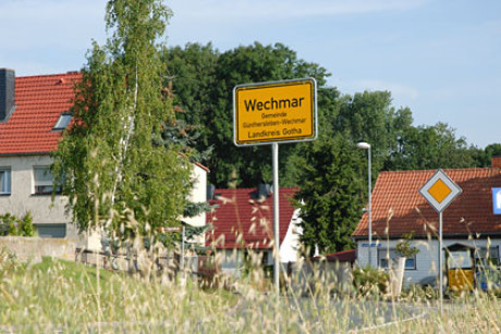 Man sieht im Bild zum Kapitel Ursprung drei aktuelle Wohnhäuser im Hintergrund. Der Fokus liegt auf dem gelben Ortseingangsschild und dem Verkehrszeichen Vorfahrt. Fotografiert ist aus einem Kornfeld.